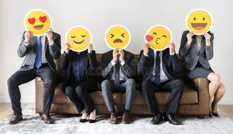 Affärsfolk som sitter samman med symboler arkivfoto