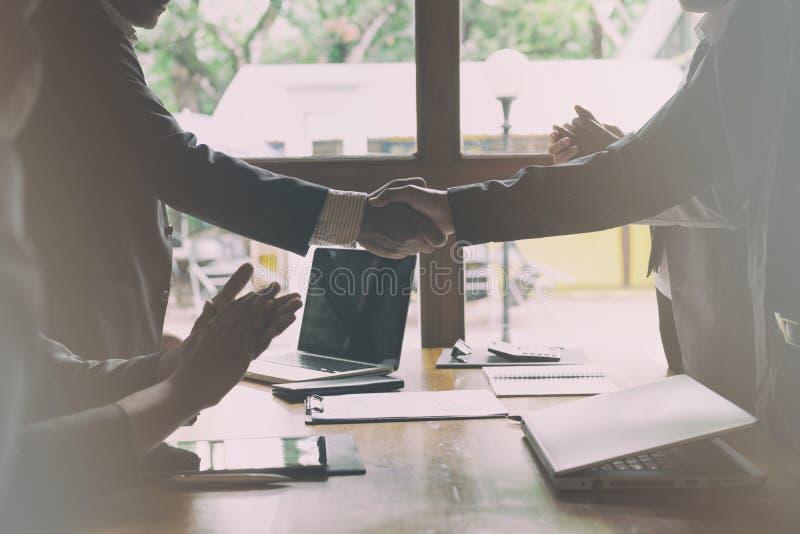 Affärsfolk som skakar händer efter fulländande övre ett möte Busi arkivfoto