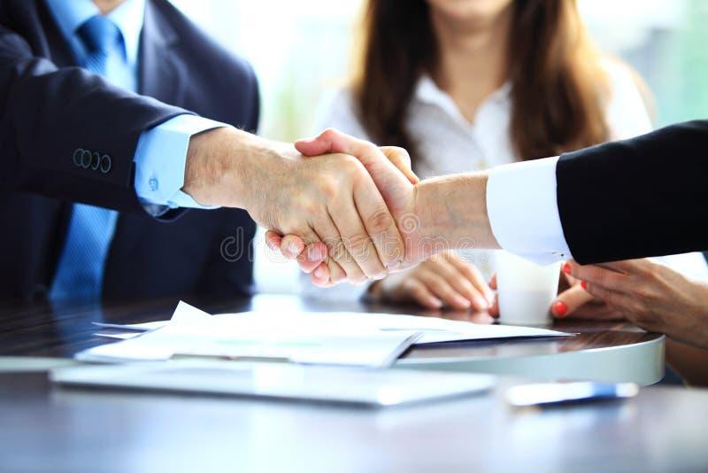 Affärsfolk som skakar händer, fulländande övre ett möte royaltyfri fotografi