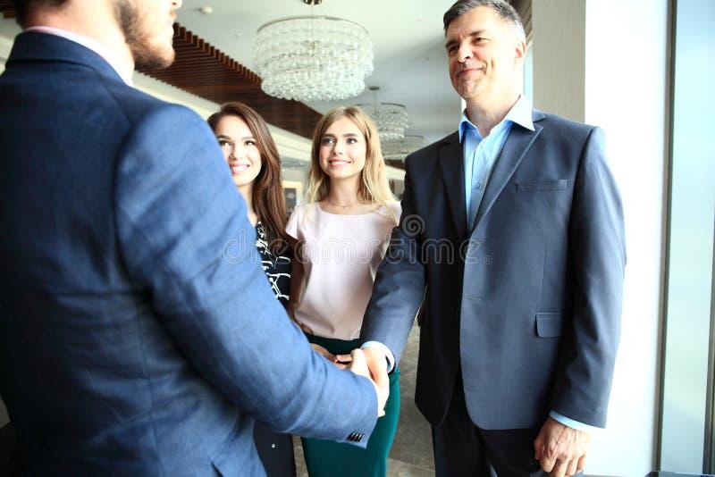 Affärsfolk som skakar händer, fulländande övre ett möte arkivfoton