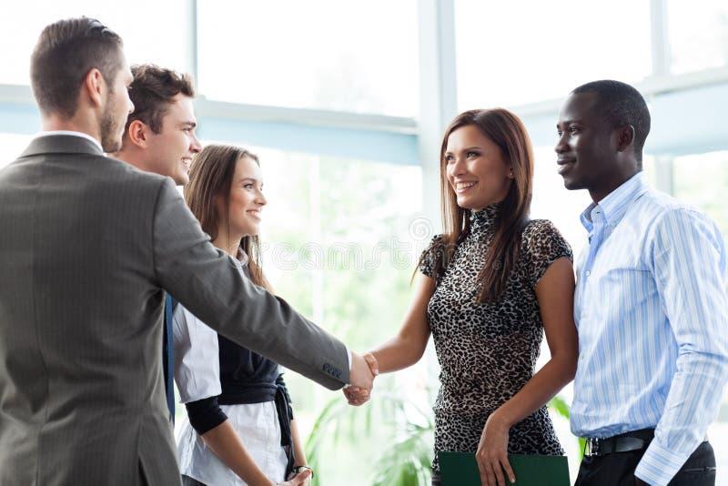 Affärsfolk som skakar händer, fulländande övre ett möte royaltyfri foto