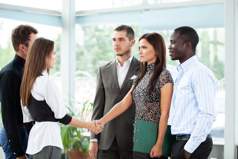 Affärsfolk som skakar händer, fulländande övre ett möte royaltyfria foton