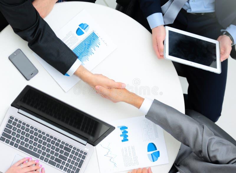 Affärsfolk som skakar händer, fulländande övre ett möte arkivbild