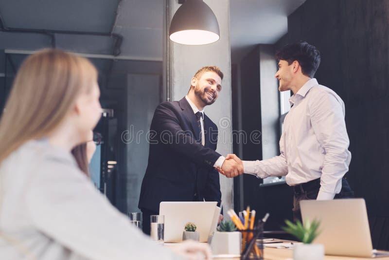 Affärsfolk som skakar händer, fulländande övre möte arkivfoton