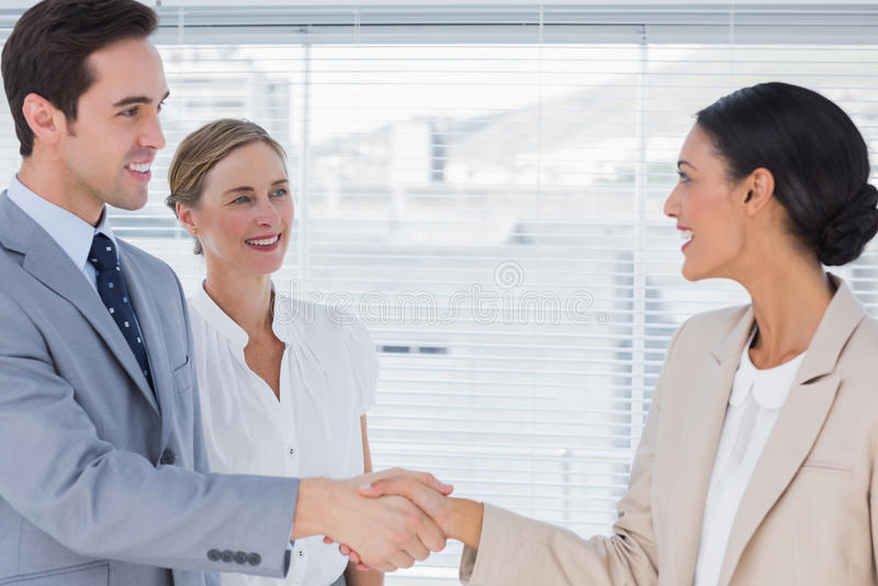 Affärsfolk som skakar händer i kontoret arkivbild