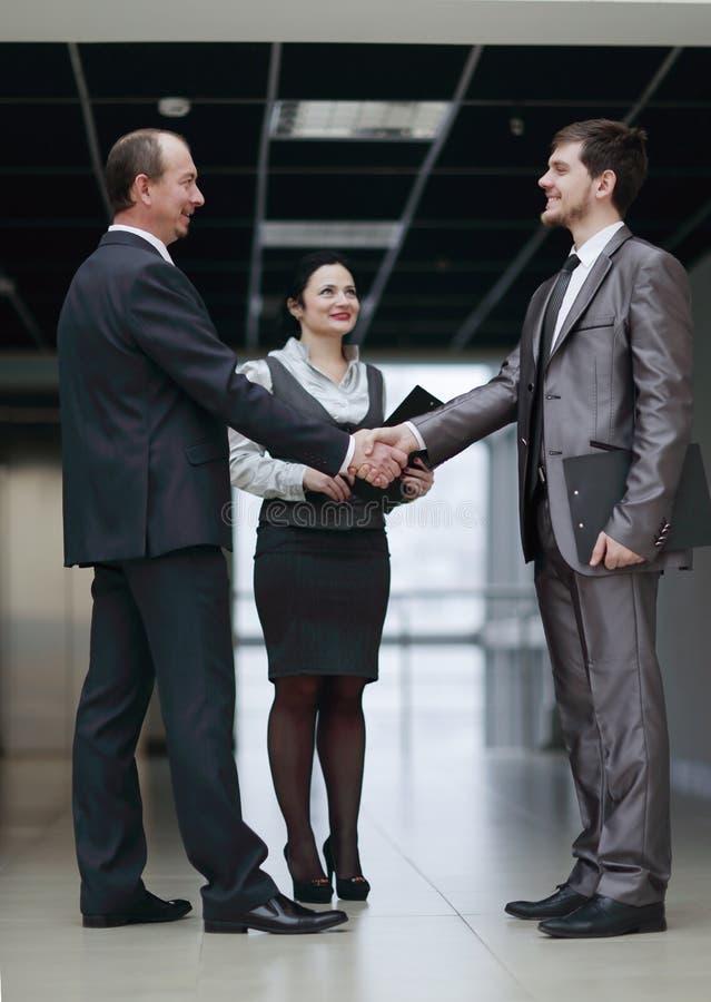 Affärsfolk som skakar händer som kommer till en överenskommelse i kontoret arkivfoton