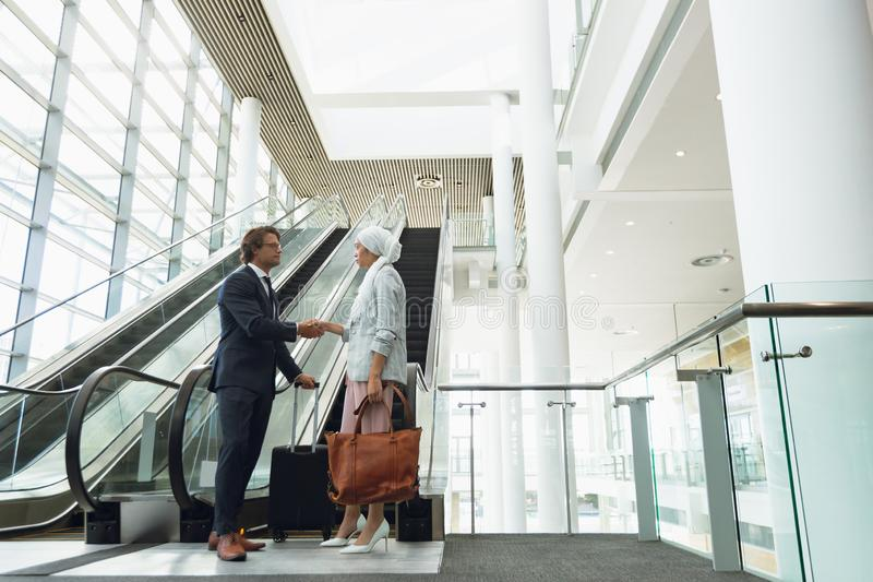 Affärsfolk som skakar händer med de nära rulltrappan i ett modernt kontor arkivfoto