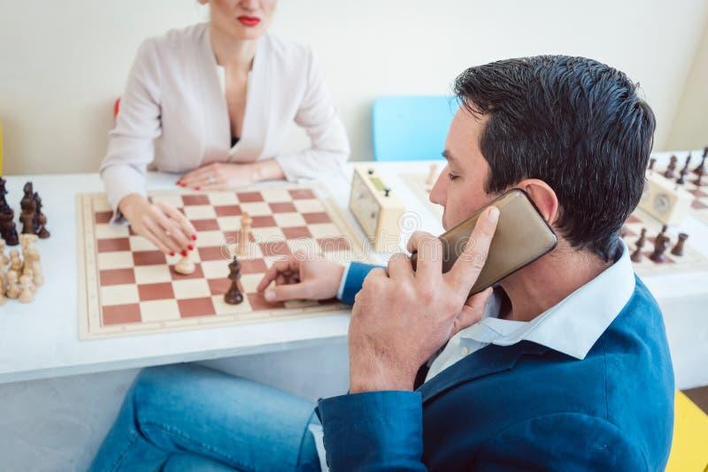 Affärsfolk som spelar schack med mannen på telefonen royaltyfria bilder