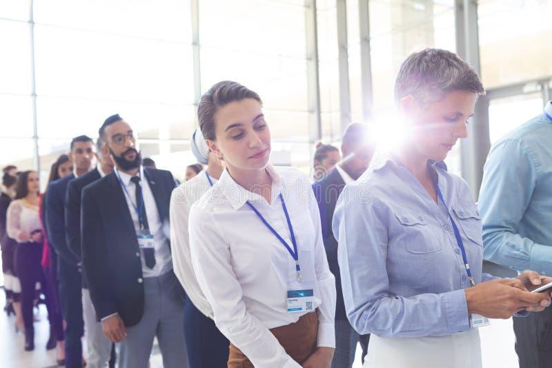 Affärsfolk som står i kö i lobby royaltyfria bilder