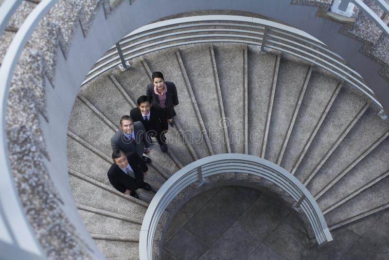 Affärsfolk som står på spiraltrappuppgång arkivbild