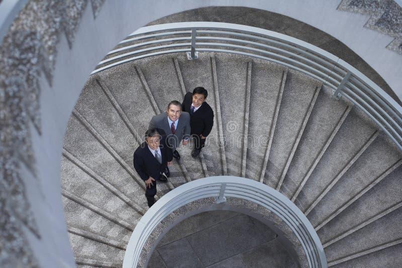 Affärsfolk som står på spiraltrappuppgång royaltyfri foto