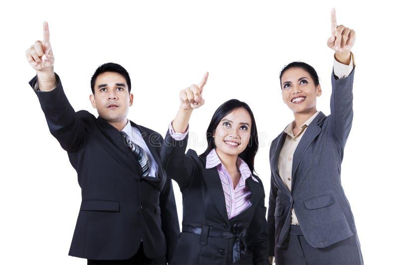 Affärsfolk som står peka och se tillsammans upp arkivbild