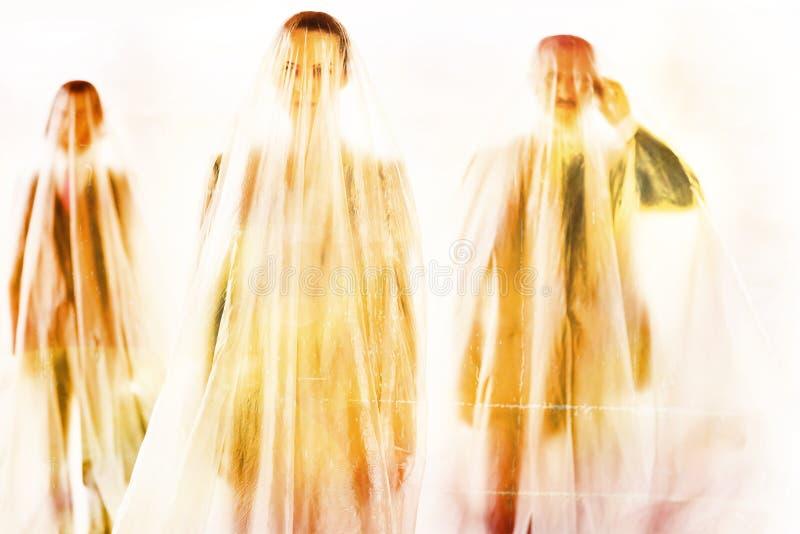Affärsfolk som står under plastskydd för att skydda sig mot Coronavirus arkivbilder