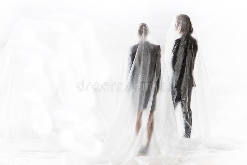 Affärsfolk som står under täckningen med plast för att skydda sig mot Coronavirus arkivbild