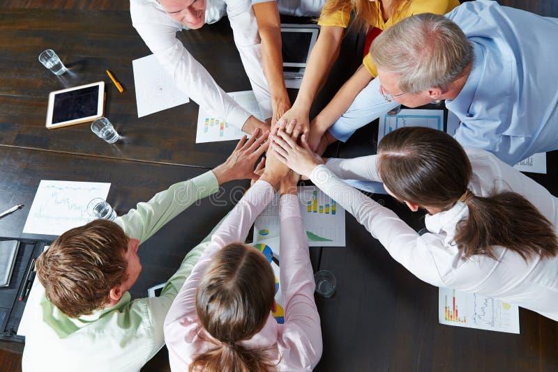 Affärsfolk som staplar händer som teamworkbegrepp royaltyfri bild