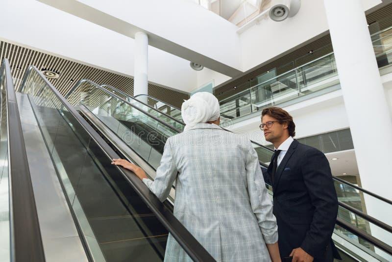 Affärsfolk som talar med de på rulltrappan i ett modernt kontor arkivfoto