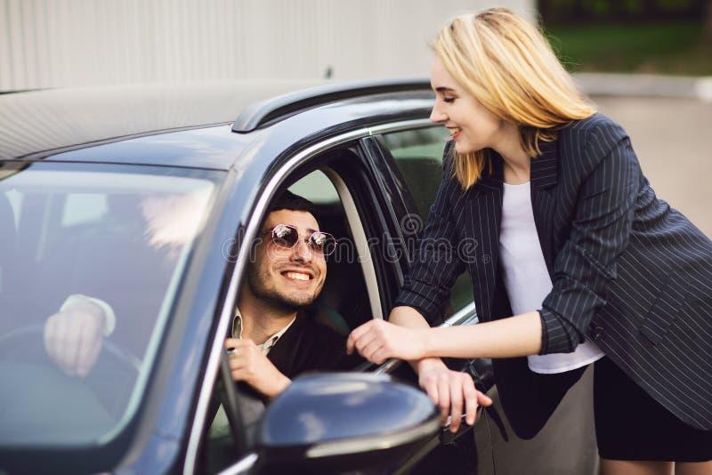 Affärsfolk som talar nära parkeringshus Mannen i exponeringsglasen sitter i bilen, kvinnan står bredvid honom royaltyfria bilder