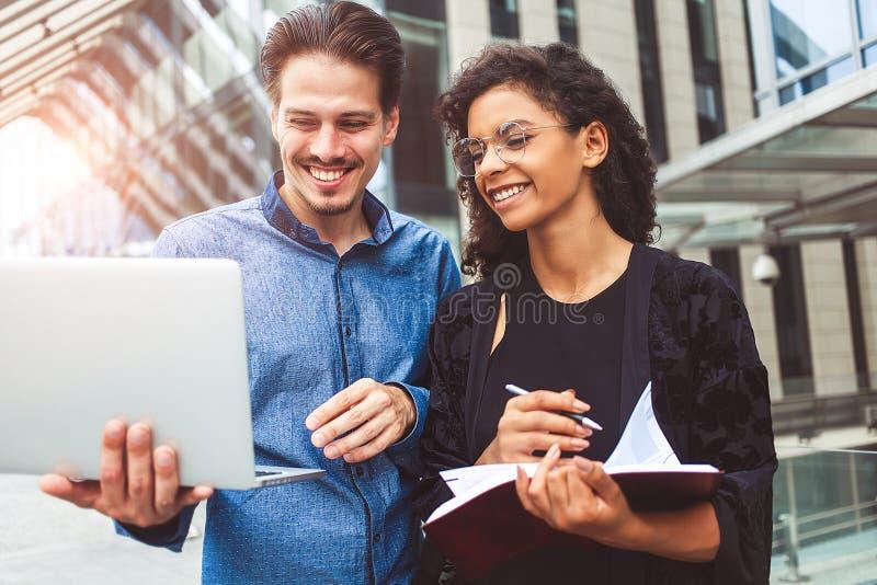 Affärsfolk som talar på gatan genom att använda en bärbar dator royaltyfri fotografi