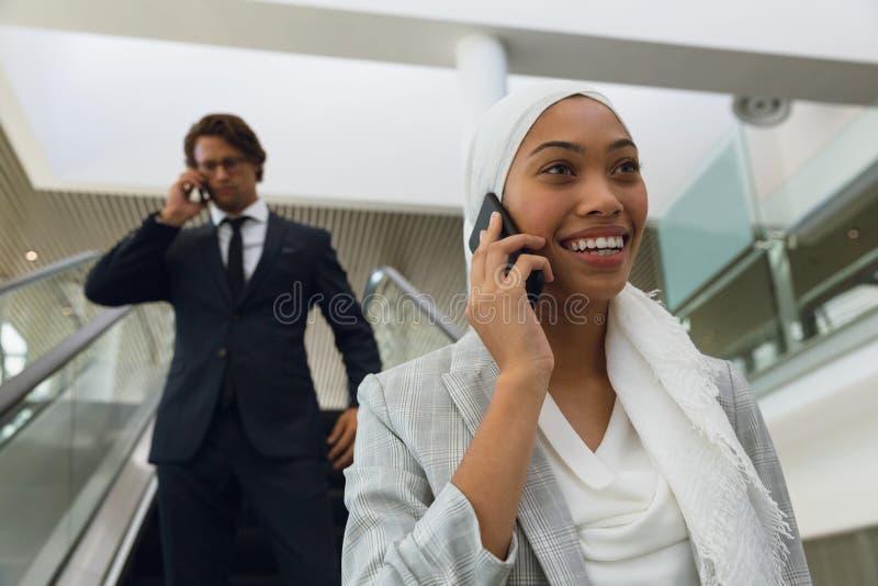 Affärsfolk som talar på mobiltelefonen på rulltrappan i ett modernt kontor arkivbild