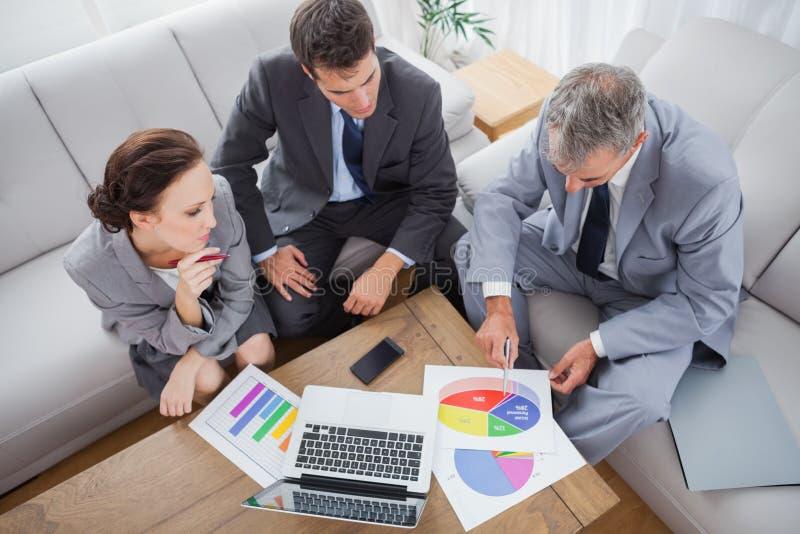 Affärsfolk som tillsammans analyserar diagram royaltyfri fotografi