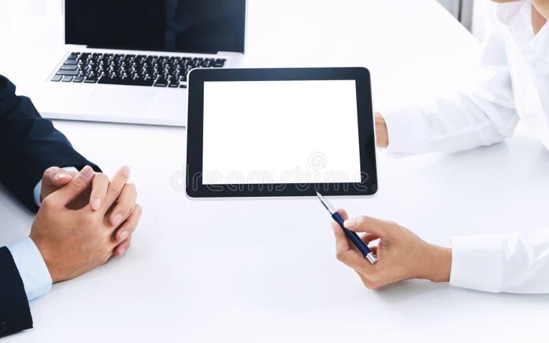 Affärsfolk som tillsammans arbetar och använder den digitala minnestavlan för tom skärm på en arbetsplats arkivbild