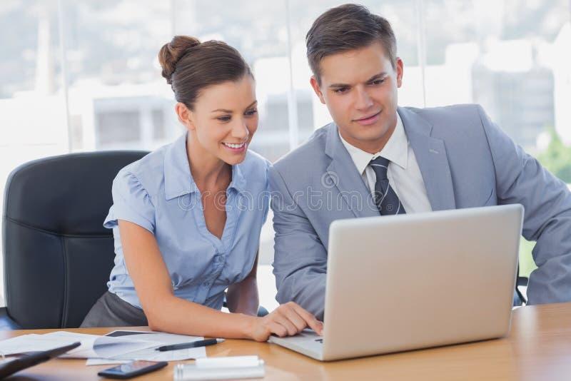 Affärsfolk som tillsammans arbetar på bärbara datorn och att le royaltyfria bilder