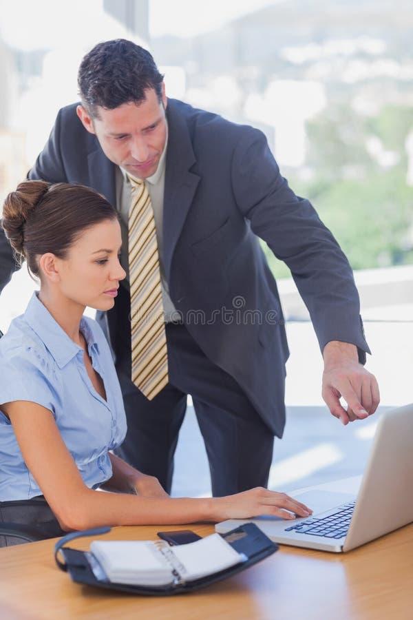 Affärsfolk som tillsammans arbetar på den samma bärbara datorn royaltyfri fotografi