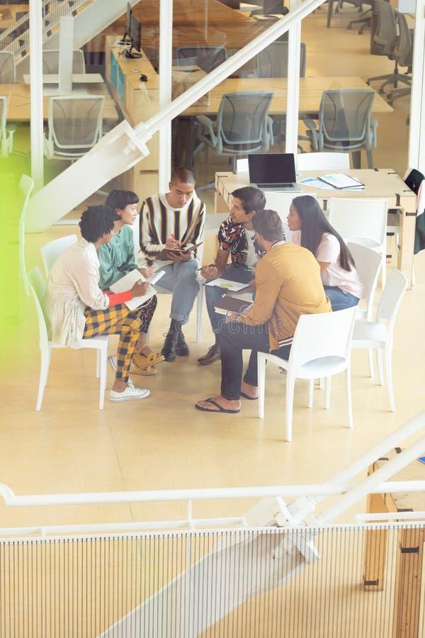 Affärsfolk som tillsammans i regeringsställning sitter och har gruppdiskussion royaltyfria bilder