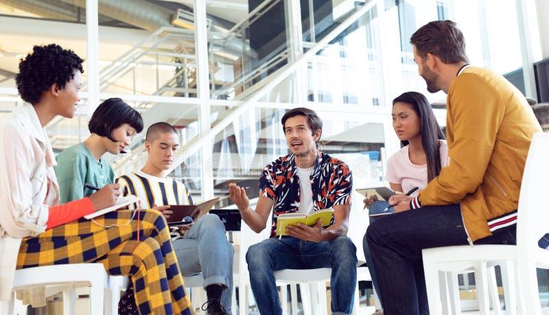 Affärsfolk som tillsammans i regeringsställning sitter och har gruppdiskussion arkivfoton