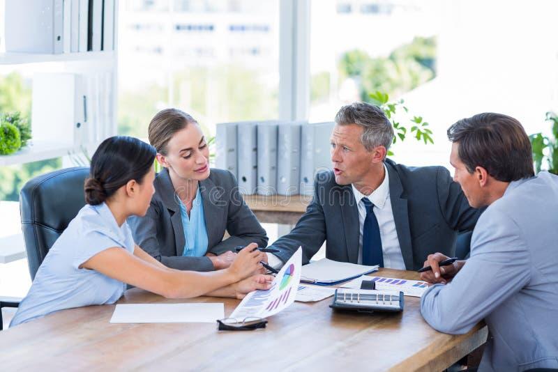 Affärsfolk som tillsammans talar under möte arkivfoton