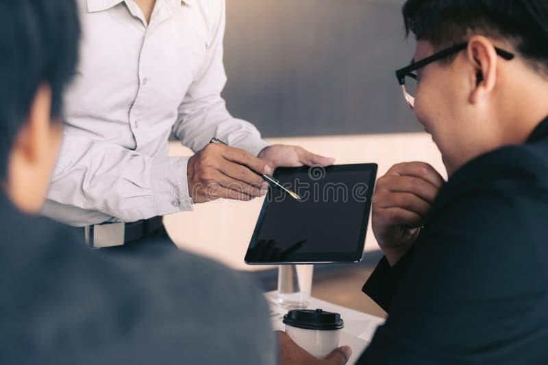 Affärsfolk som undersöker finansiella rapporter och analyserar affärstillväxt i minnestavlaskärm fotografering för bildbyråer