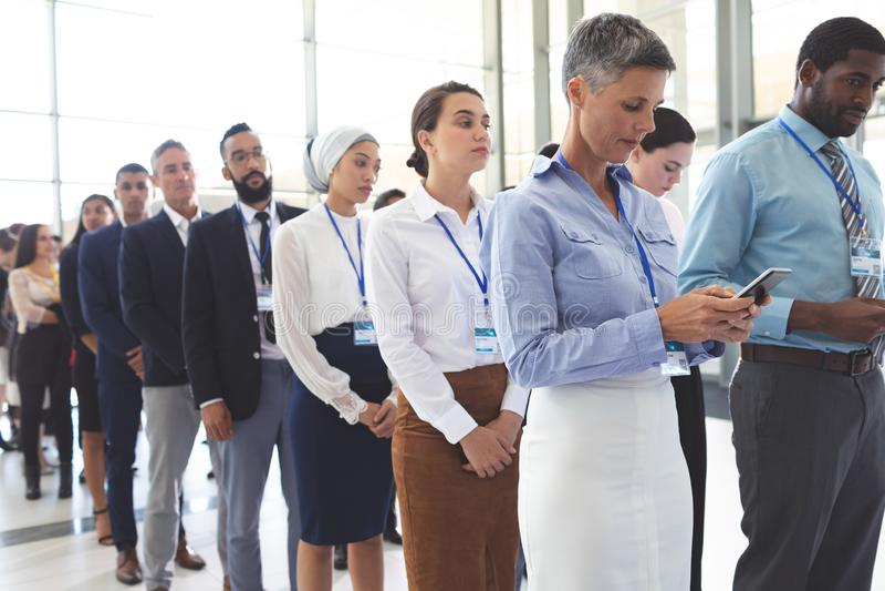 Affärsfolk som väntar i kö i lobby arkivbild
