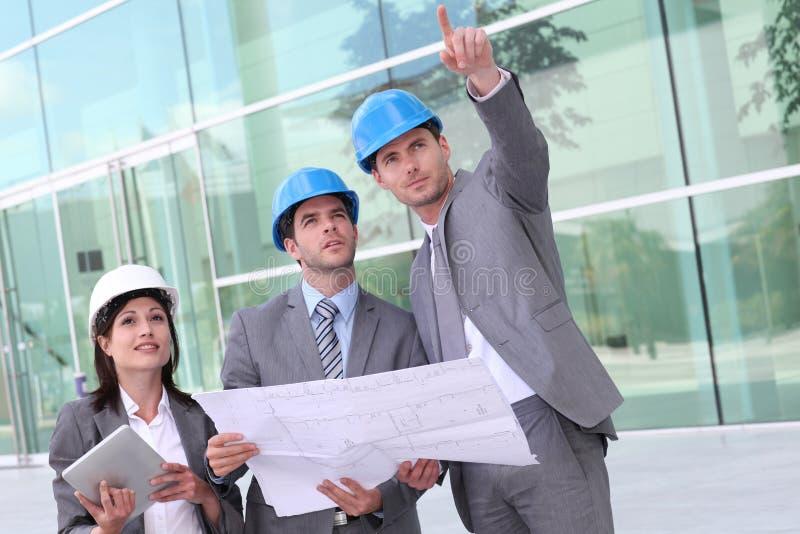 Affärsfolk som verifierar byggnadskonstruktion arkivfoto