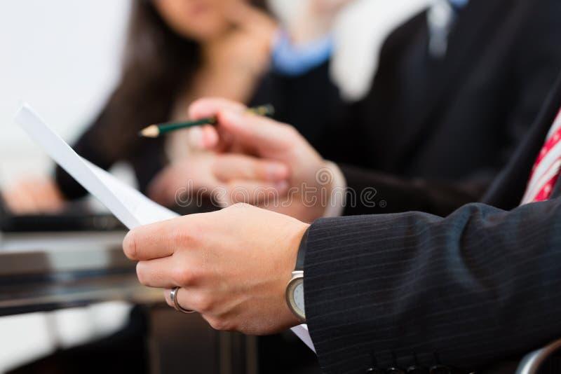 Affärsfolk under möte i regeringsställning royaltyfria bilder