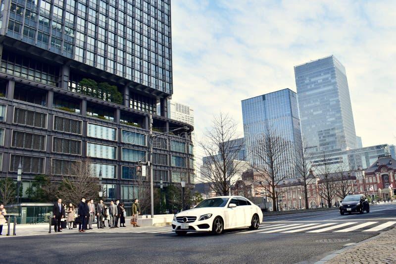Affärsfolket går över tvärgatan på den Tokyo stationen royaltyfria foton