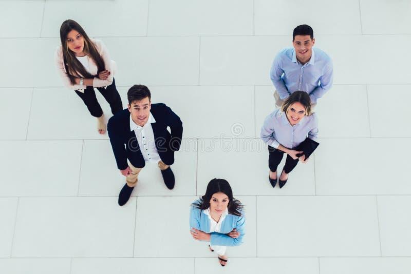 Affärsfolket grupperar det lyckliga leendet som står på den bästa sikten för det moderna kontoret, royaltyfri fotografi
