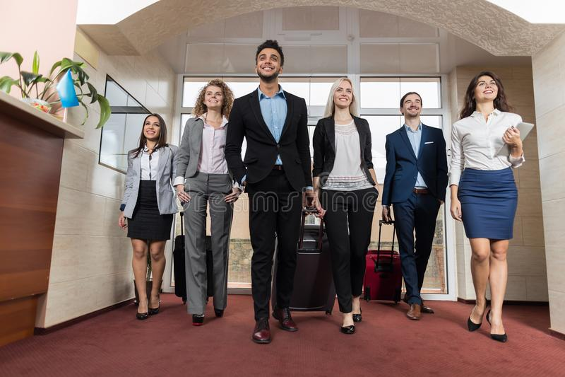 Affärsfolket i hotelllobby, gäster för grupp för blandningloppBusinesspeople ankommer royaltyfria bilder
