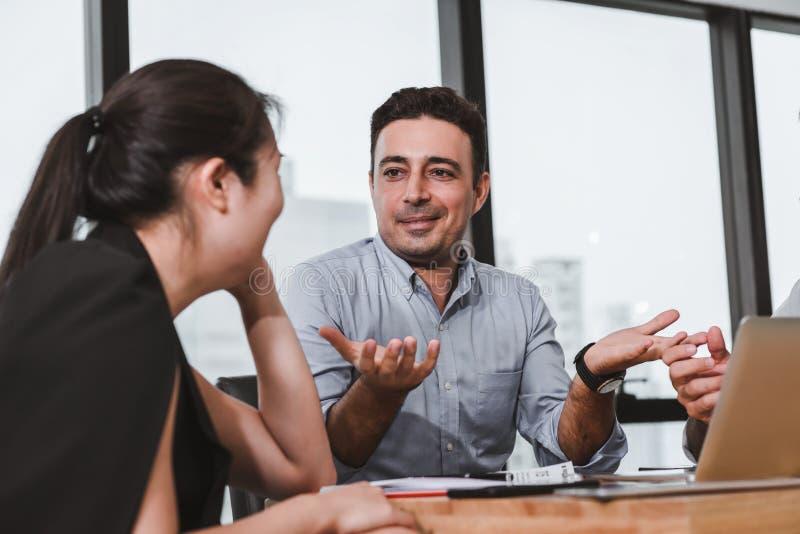 Affärsfolket möter att diskutera om deras projekt, och problemlösning i konferensrum, den yrkesmässiga chefen är arkivbild