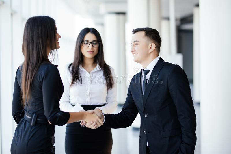 Affärsfolket man och kvinnan som skakar händer, fulländande övre ett möte arkivbilder