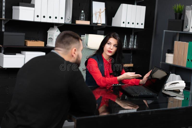 Affärsfolket ser den tomma bärbar datorskärmen på möte i stilfullt kontor arkivfoto