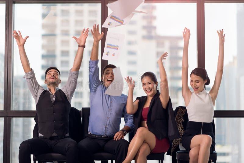 Affärsfolket som firar, genom att kasta deras affärslegitimationshandlingar och dokument, flyger i luft, makt av samarbete, framg fotografering för bildbyråer