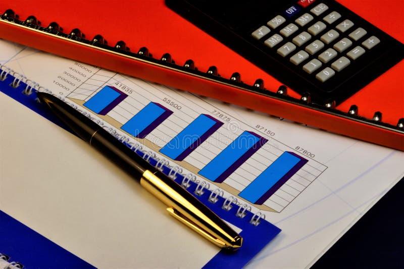 Affärsgraf av att växa upp, en räknemaskin, en röd mapp med viktigt rapporter och arbetsplan, en penna och en anteckningsbok av arkivbilder