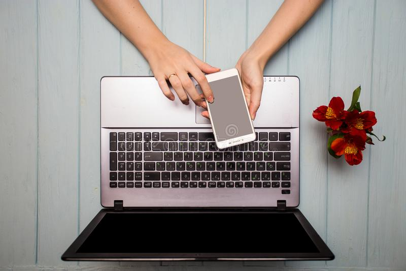 Affärshandkvinna som använder telefonen, den moderna tabellen för kontorsskrivbord med bärbara datorn, koppen kaffe och blommor royaltyfri fotografi