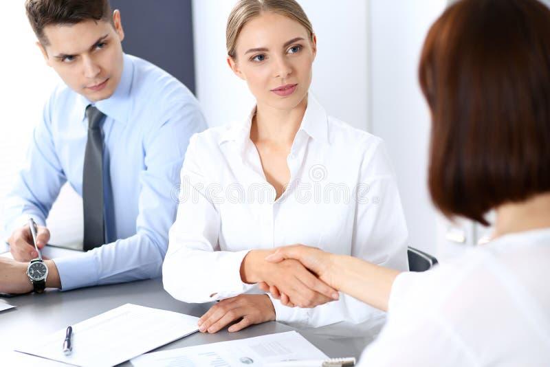 Affärshandskakning av den blonda kvinnan och hennes partner på mötet Begrepp av framgång och överenskommelse royaltyfri foto