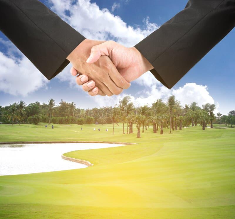Affärshandskakning på golfbana fotografering för bildbyråer