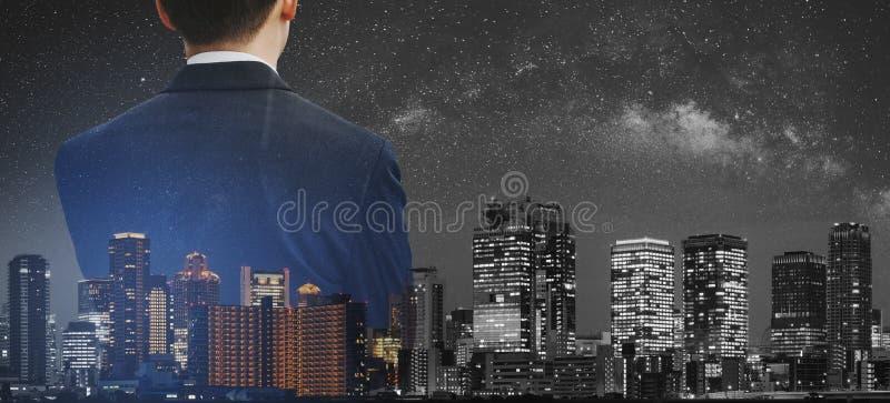 Affärsidé affärsman i svart dräkt med den panorama- moderna staden för dubbel exponering på natten arkivbilder