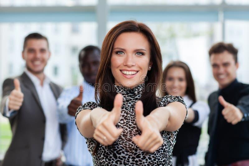 Affärsidé - attraktiv affärskvinna med laget i regeringsställning som visar upp tummar arkivbilder