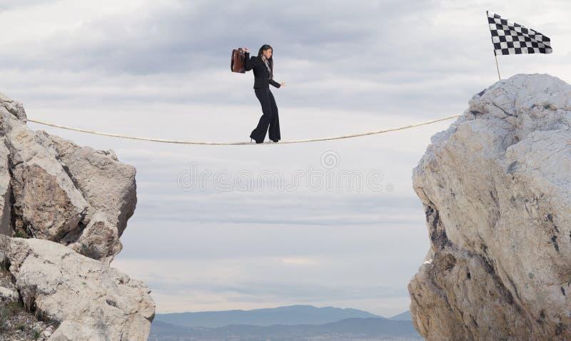 Affärsidé av affärskvinnan som övervinner problemen som når flaggan på ett rep fotografering för bildbyråer