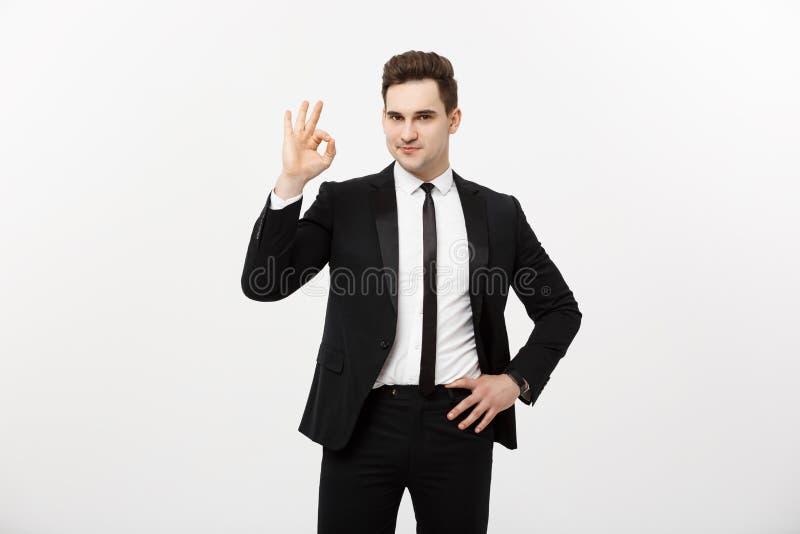 Affärsidé: En stilig man i smart dräkt på grå bakgrund som visar det ok tecknet arkivbilder