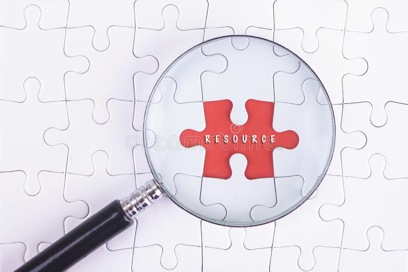 Affärsidé - förstoringsapparatexponeringsglas på vit puzze med RESURSord royaltyfria foton